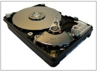 Hard disk drive with cover removed, showing the pgm-containing disk in which information is stored